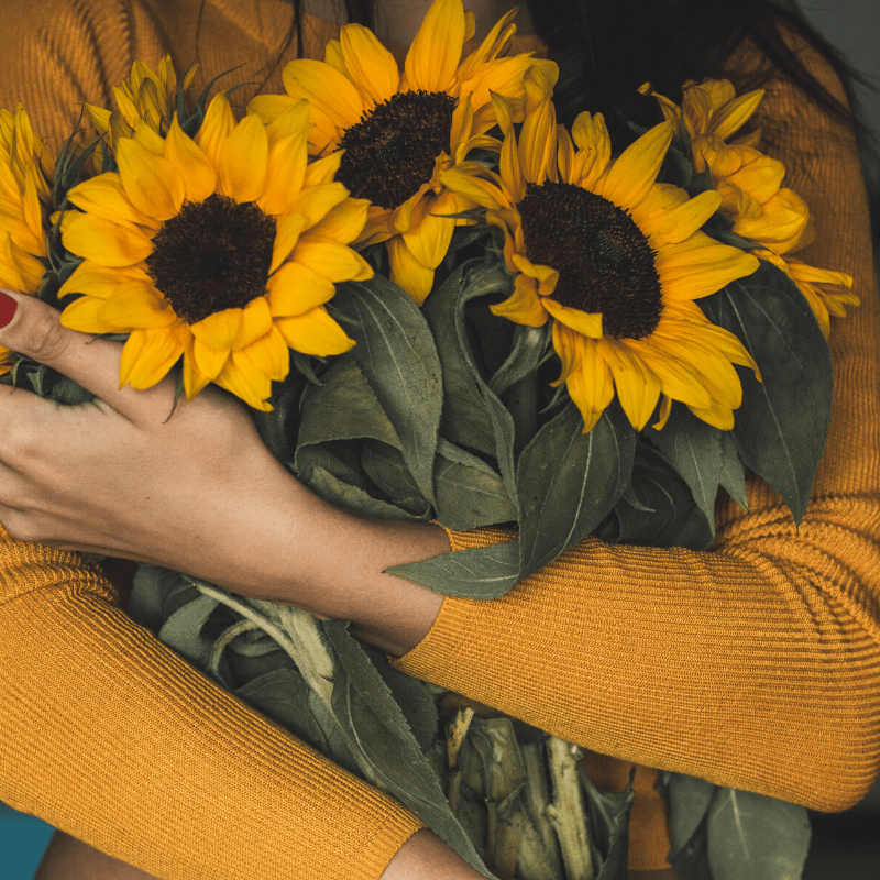Woman holding sunflowers